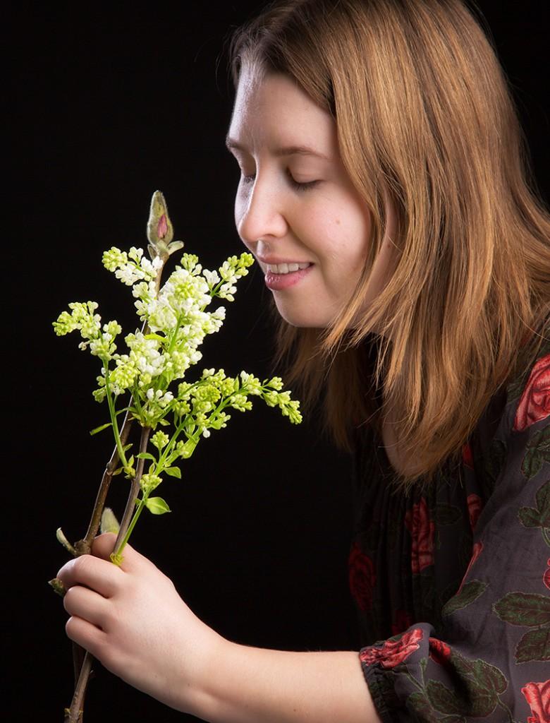 Norrländska Trädgårdars grundare, Emma Ershag, njuter av doften från en vacker blomsterkvist.